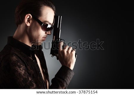 Portrait of a handsome young man holding a gun..