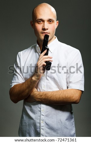 Portrait of a handsome young man holding a gun