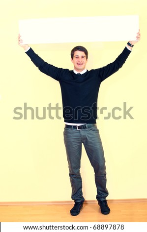 Portrait of a handsome young man holding empty sheet over head against uniform background