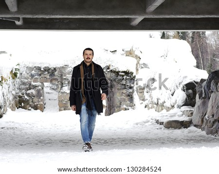 Portrait of a handsome young man in a full-length on the street in winter