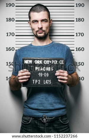 Portrait of a handsome young man in a police station. In his hands he holds a plaque with data. In the background, a ruler for measuring growth is visible on the wall. The guy is shortly tonsured and