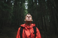 Portrait of a handsome young man in a red jacket stands in the evening forest with his head up, looking with a serious face. Closeup portrait of young hiker hiking, looking up at trees. Mountain trip.