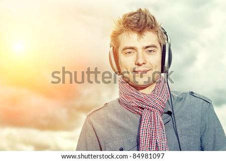Portrait of a handsome young man in headphones posing outdoor.