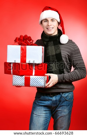 Portrait of a handsome young man in Santa Claus hat holding presents. Christmas.