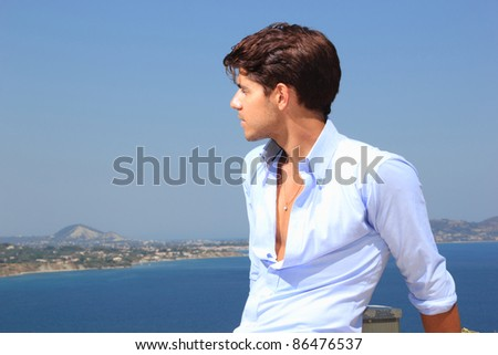 Portrait of a handsome young man in the sun by the sea