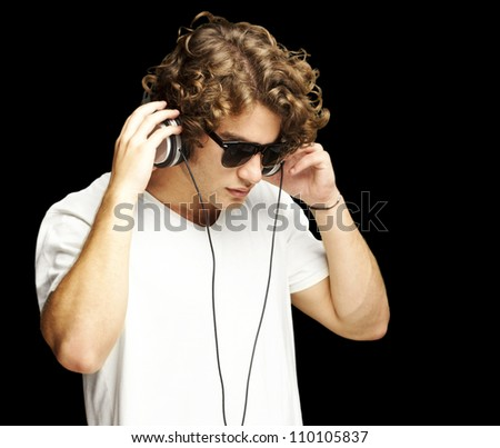 portrait of a handsome young man listening music against a black background