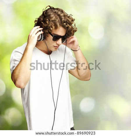 portrait of a handsome young man listening music against a nature background - stock photo