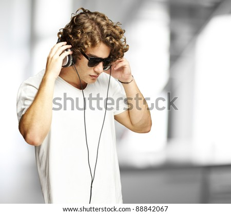 portrait of a handsome young man listening music indoor