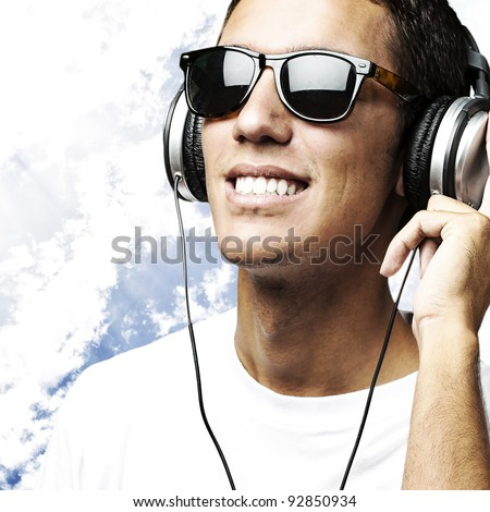 portrait of a handsome young man listening to music against a blue sky background