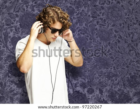 portrait of a handsome young man listening to music against a vintage background