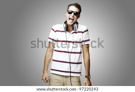 portrait of a handsome young man listening to music over a grey background
