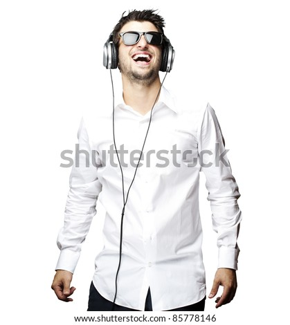 portrait of a handsome young man listening to music with headphones over white