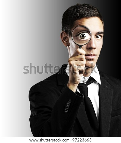 portrait of a handsome young man looking through a magnifying glass against a black background