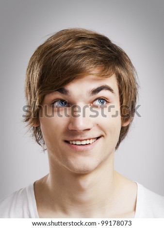 Portrait of a handsome young man, over a gray background - stock photo