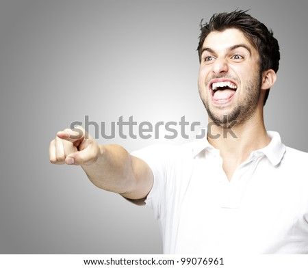 portrait of a handsome young man pointing and joking over grey background