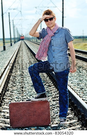 Portrait of a handsome young man posing at a railroad.