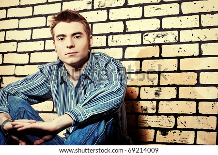 Portrait of a handsome young man posing over brick wall.