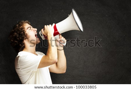 portrait of a handsome young man shouting with a megaphone against a grunge background