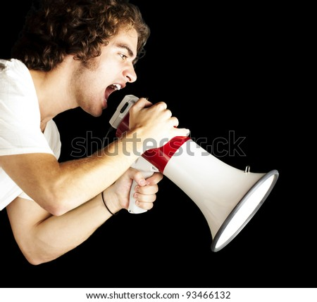 portrait of a handsome young man shouting with megaphone against a black background