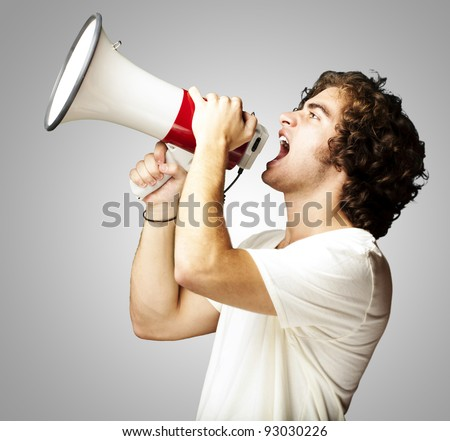 portrait of a handsome young man shouting with megaphone against a grey background