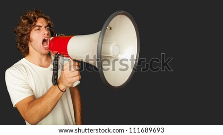 Portrait Of A Handsome Young Man Shouting With Megaphone On Black Background