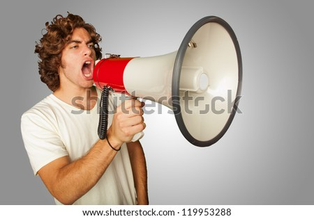 Portrait Of A Handsome Young Man Shouting With Megaphone On Gray Background