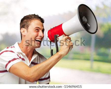 Portrait Of A Handsome Young Man Shouting With Megaphone, Outdoor