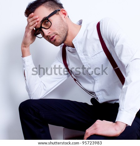 portrait of a handsome young man sitting in white shirt and suspenders against white background