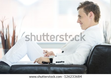 Portrait of a handsome young man sitting on couch indoor