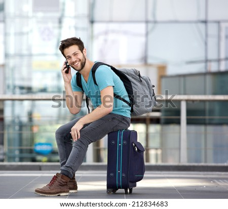 Portrait of a handsome young man sitting on suitcase and calling by cellphone at airport #212834683