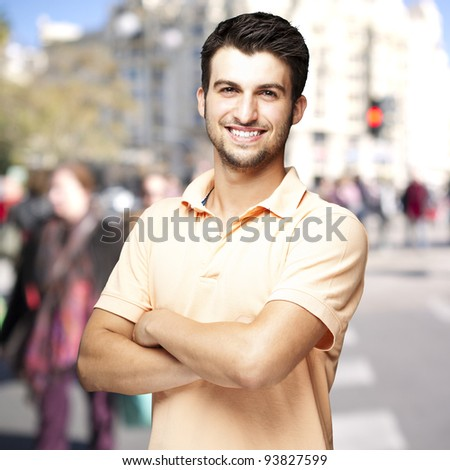 portrait of a handsome young man smiling against a crowded street background