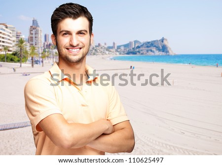 portrait of a handsome young man standing against a beach
