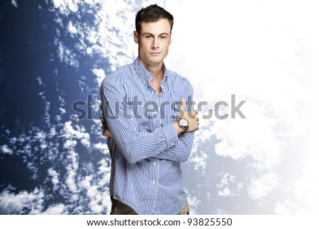 portrait of a handsome young man standing against a cloudy sky background #93825550