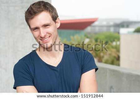 portrait of a handsome young man standing outside