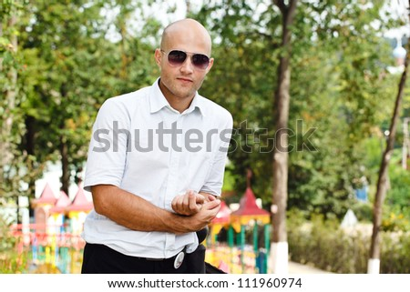 portrait of a handsome young man wearing sunglasses against a nature background