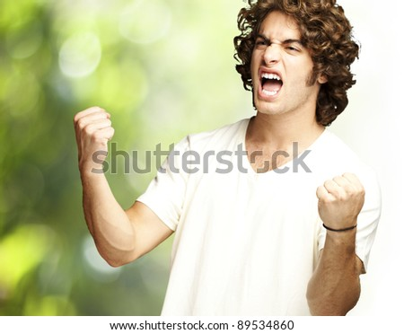 portrait of a handsome young man winning against a nature background