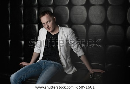 Portrait of a handsome young man with red hair sitting on a black leather sofa
