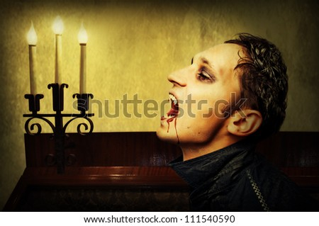 Portrait of a handsome young man with vampire style make-up. - stock photo