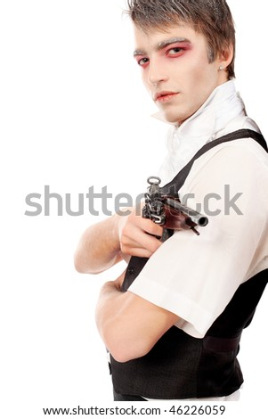 Portrait of a handsome young man with vampire style make-up, holding a gun in his hand. Shot in a studio.