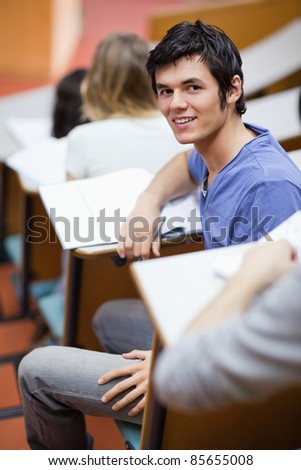 Portrait of a handsome young student being distracted in an amphitheater