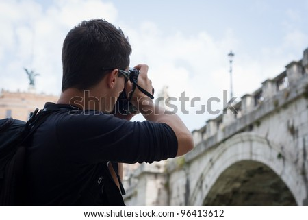 Portrait of a handsome young tourist taking photographs while sightseeing in Rome, Italy (with the Sant'Angelo bridge and castel in the background)
