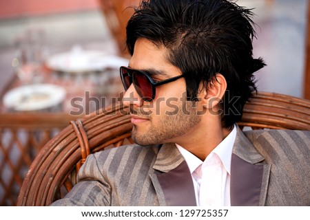 portrait of a hansome bi racial young man wearing sunglasses in outdoor, serious young man