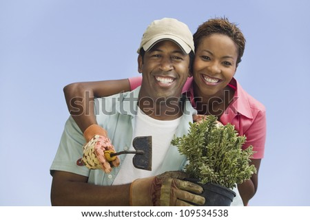 Portrait of a happy African American couple gardening against clear sky - stock photo
