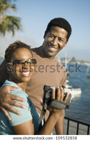 Portrait of a happy African American couple with woman holding handy cam