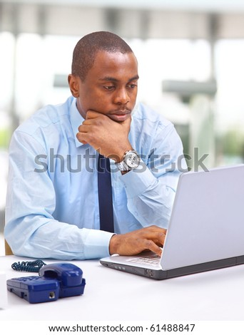 Portrait of a happy African American entrepreneur displaying computer laptop