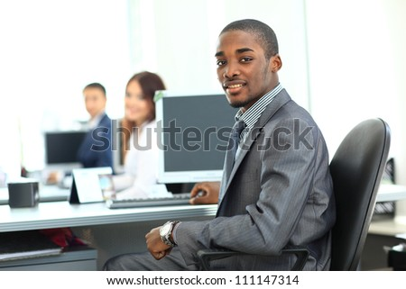 Portrait of a happy African American entrepreneur displaying computer laptop in office