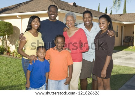 Portrait of a happy African American family standing together in front of the house