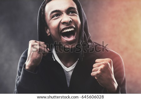 Portrait of a happy African American young man wearing a black hoodie and making a victory gesture. Toned image