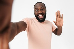 Portrait of a happy african man wearing t-shirt standing isolated over white background, taking selfie, waving hand
