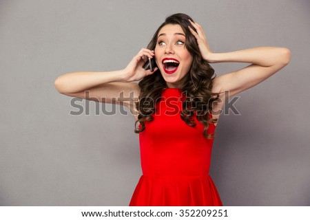 Portrait of a happy amazed woman in red dress talking on the phone over gray background